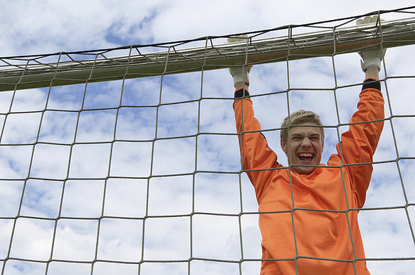 Cheering Goalkeeper Hanging On Goal Photograph by Stock4b-rf