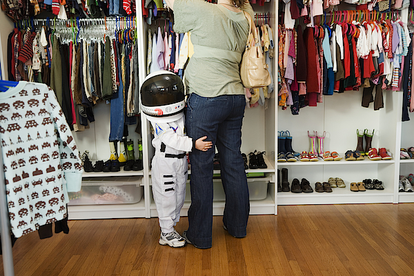 Child (4-5 Yeras) Wearing Space Costume Hugging Mothers Leg In Shop Photograph by Inti St. Clair