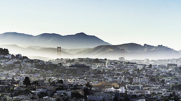 Cityscape By Mountains Against Clear Sky During Foggy Weather Photograph by Jesse Coleman / EyeEm