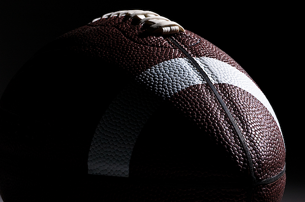 Close-up Of American Football With Dramatic Lighting Photograph by Kledge