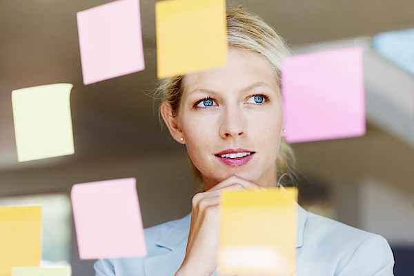 Contemplative Business Woman With Sticky Notes On Glass Window Photograph by GlobalStock