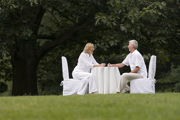 Couple Dining Outdoors Photograph by Comstock Images