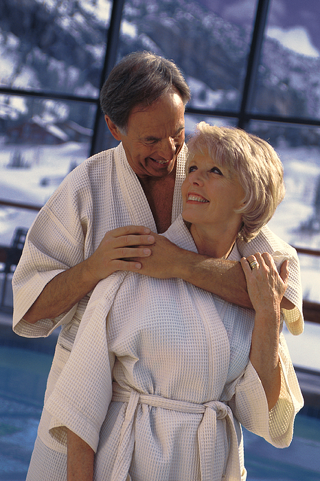 Couple Hugging Near Indoor Pool At Resort Photograph by Comstock