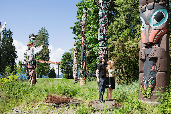 Couple Looking At Totem Poles Photograph by Image Source