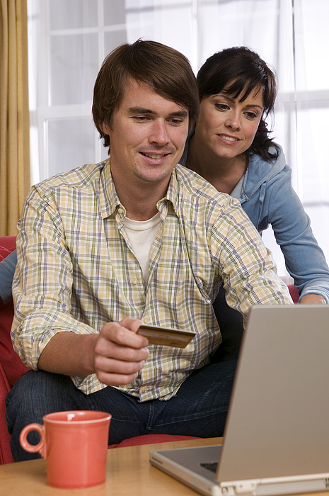 Couple With Credit Card Using Laptop Photograph by Comstock Images