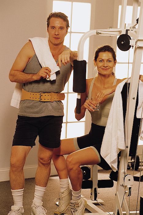 Couple With Exercise Equipment At Health Club Photograph by Comstock