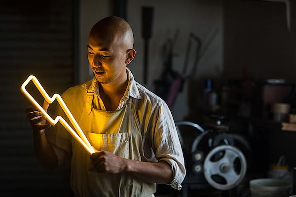Craftsmen Holding A Lightning Bolt Shaped Neon Light Photograph by Trevor Williams