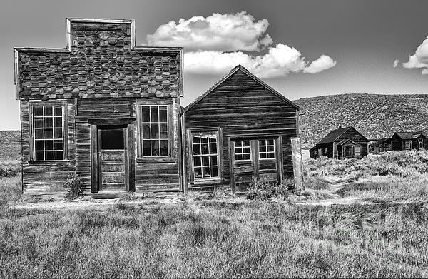 Black & White;black + White;monochrome;black And White;architecture;detail;details;cabins;structures;wood;windows;doors;door;window;buildings;dilapidated;rundown;abandoned;forlorn;derelict;empty;sandra Bronstein;clouds;doorways;entrances;old West;out West;bodie;ghost Town;ghost Towns;california;gold Rush Days;mining;houses;house;residence;horizontal;fine Art Photography;iconic;travel;tourism;historical;state Park;popular;dated;unoccupied;panes;glass;western United States;canvas; Photograph - Days Of Glory Gone by Sandra Bronstein