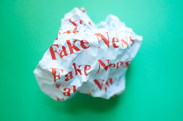 Fake News Against Blue Green Background Photograph by Karl Tapales