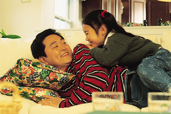 Father And Daughter On Sofa Photograph by Comstock