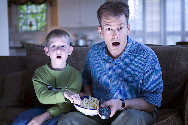 Father And Son With Remote Control And Popcorn Photograph by Thinkstock Images