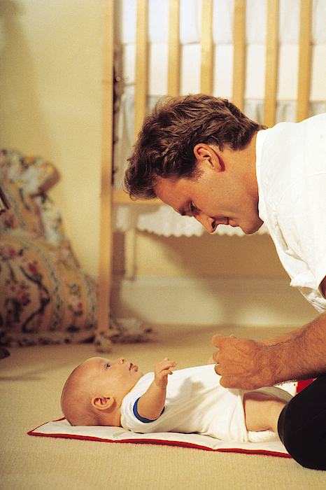 Father Changing Babys Diaper Photograph by Comstock
