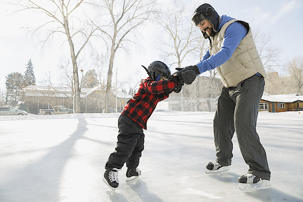 Father Teaching Son To Ice-skate On Outdoor Rink Photograph by Hero Images