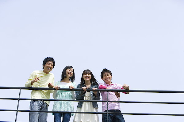 Four Young People Leaning On The Railing, Side By Side, Low Angle View, Blue Background, Copy Space, Japan Photograph by Daj