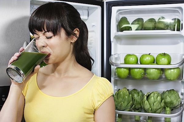 Grimacing Mixed Race Woman Drinking Healthy Drink Near Refrigerator Photograph by Jill Giardino