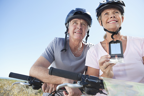 Happy Mature Woman Mountain Biking With Man Using Gps Photograph by OJO Images
