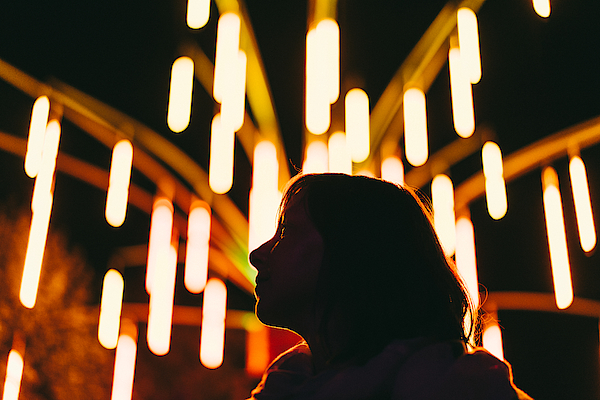 Low Angle View Of Silhouette Woman Against Illuminated Lights At Night Photograph by Adriana Duduleanu / EyeEm