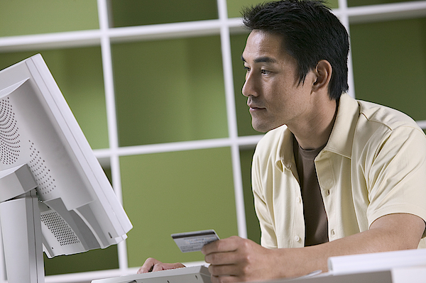 Man Ordering Online With Credit Card Photograph by Comstock Images