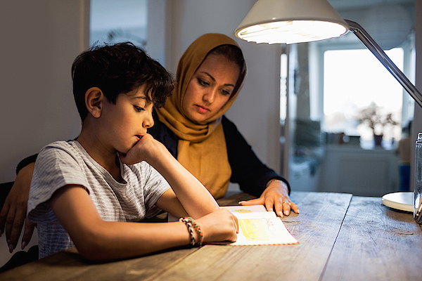 Mother And Son Reading Book Under Illuminated Desk Lamp At Home Photograph by Maskot