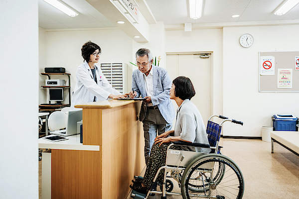 Nurse Helping Elderly Couple At Hospital Counter Photograph by TommL