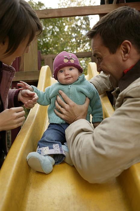 Parents With Baby Playing On Slide Photograph by Comstock Images
