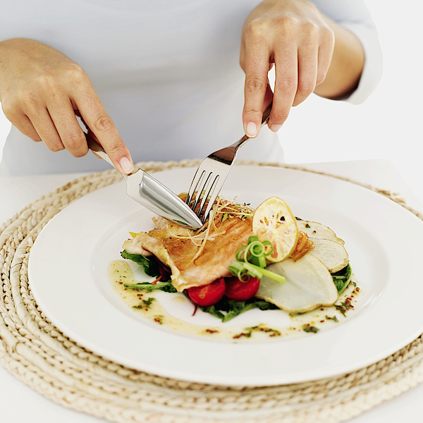 Person Using A Fork And Knife On A Plate Of Grilled Salmon Photograph by Stockbyte