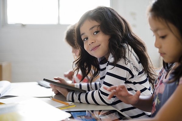 Portrait Of Smiling Girl Using Digital Tablet In Classroom Photograph by JGI/Jamie Grill