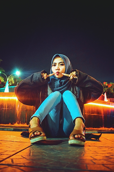 Portrait Of Young Woman Wearing Hijab While Sitting On Footpath At Night Photograph by Ilham Adhi Kusuma / EyeEm