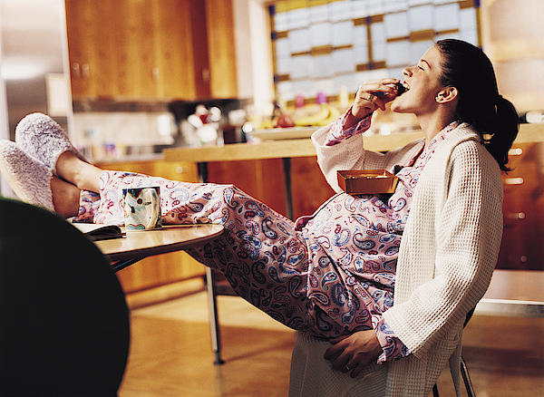 Pregnant Woman Eating Chocolate Photograph by Cohen/Ostrow
