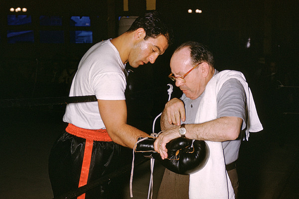 Marvin Newman Photograph - Rocky Marciano Looking At Glove by Retro Images Archive