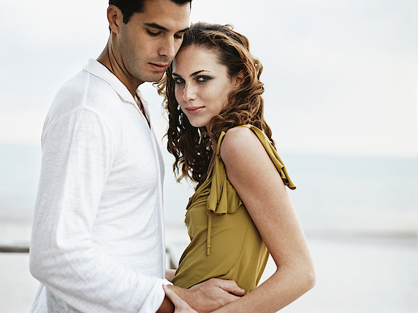 Romantic Couple Standing Together, Woman Looking At Camera Photograph by Digital Vision.