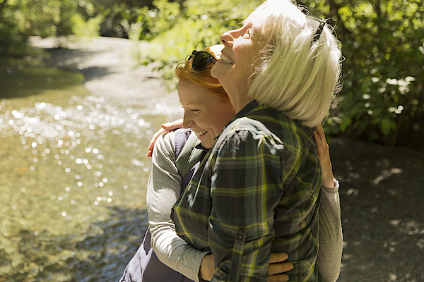 Senior Woman And Daughter Hiking Hugging By River Photograph by Compassionate Eye Foundation/Steven Errico