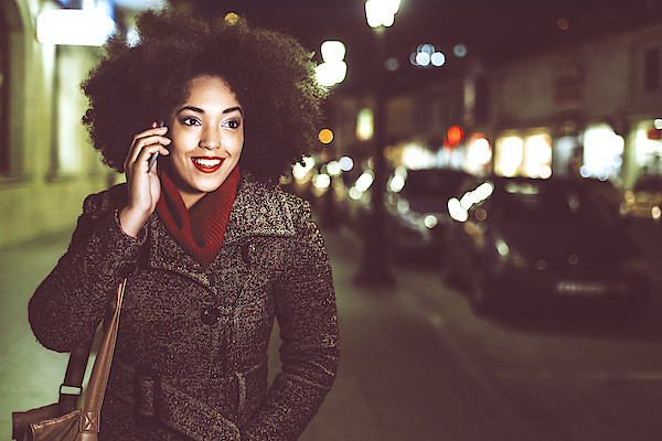 Smiling Young Woman Using Phone On Street By Night Photograph by Portishead1