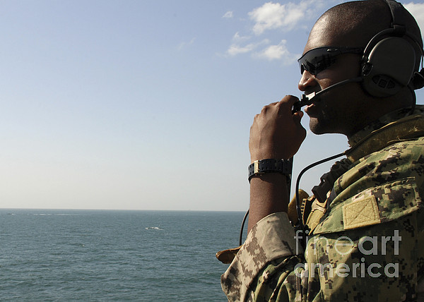 Military Photograph - Soldier Instructs Small Boat Maneuvers by Stocktrek Images