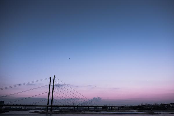 Suspension Bridge Over Sea Against Sky During Sunset Photograph by Christian Soldatke / EyeEm