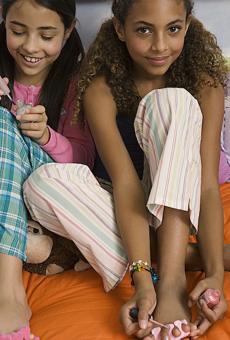 Two Preteen Girls Painting Toenails Photograph by Jupiterimages