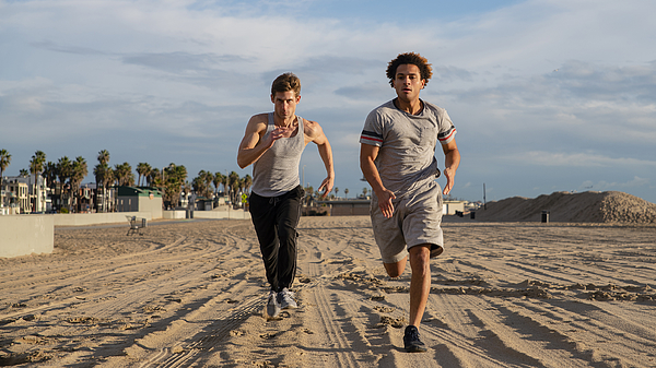 Two Young Friends Jogging At The Beach Photograph by Alex Potemkin