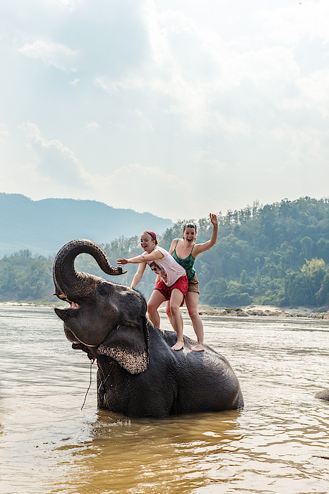Two Young Women Riding An Elephant In The Mekong Photograph by Matteo Colombo