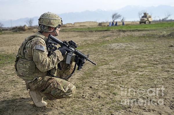 Bagram Airfield Photograph - U.s. Soldier Patrols A Village by Stocktrek Images