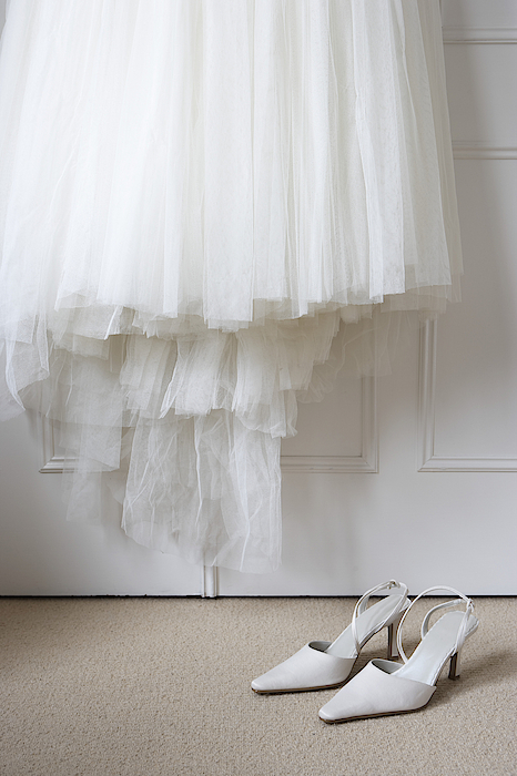 White Shoes On Floor Beneath Wedding Dress Hanging Outside Wardrobe Photograph by Michael Blann