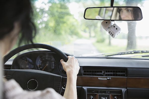 Woman Driving Car With Dice Hanging From Rear-view Mirror Photograph by Hero Images
