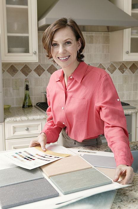 Woman In Kitchen With Tile Samples Photograph by Comstock Images