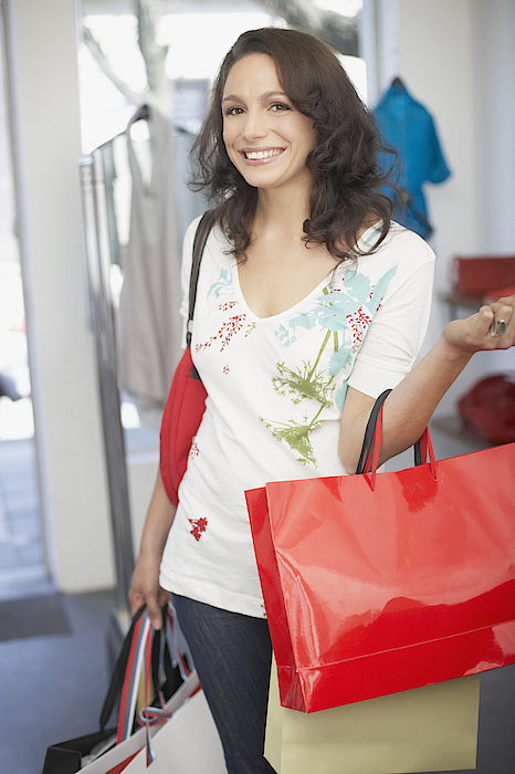 Woman In Store With Shopping Bags Smiling Photograph by Paul Bradbury