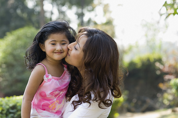 Woman Kissing Her Daughter In A Park Photograph by Photosindia