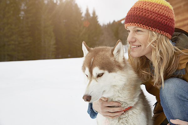 Woman Kneeling With Husky In Snow Covered Landscape, Elmau, Bavaria, Germany Photograph by Stephen Lux