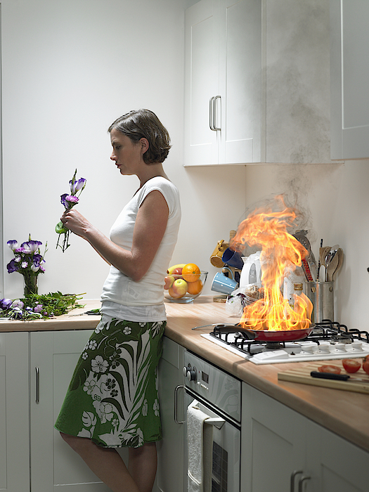 woman Leaning Against Kitchen Worktop Holding Flower, Frying Pan On Fire Behind Photograph by Michael Blann
