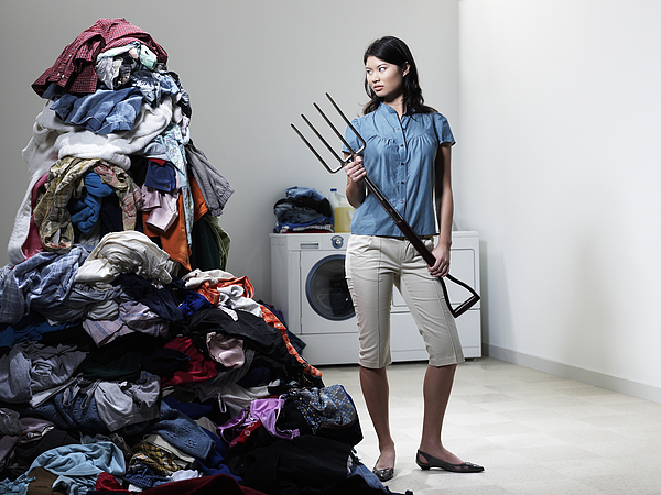 Woman Next To Pile Of Laudry With Pitchfork. Photograph by Ryan McVay