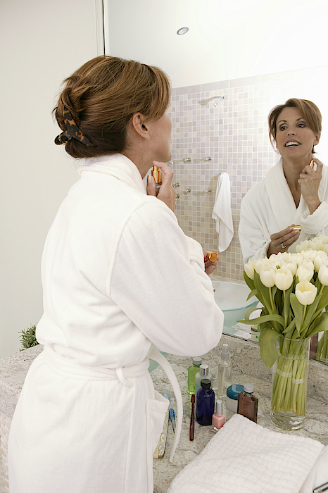 Woman Putting On Perfume Photograph by Comstock Images
