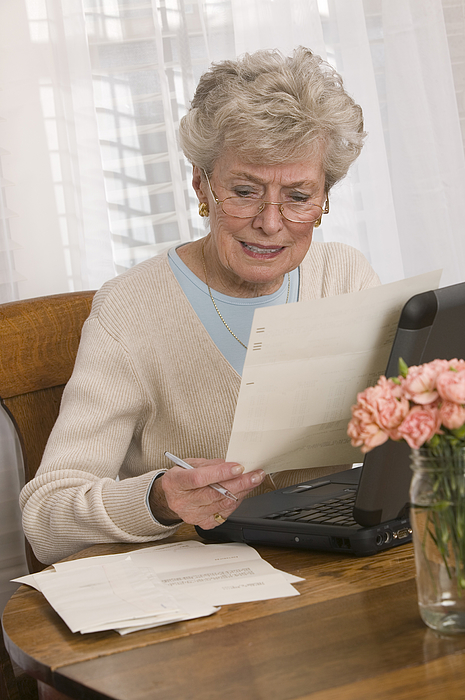 Woman Reading And Using Laptop Photograph by Comstock Images
