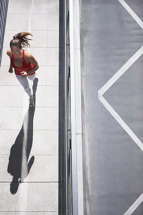 Woman Running On Urban Sidewalk Photograph by Paul Bradbury